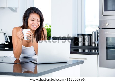 Woman checking her emails in the morning on a laptop - stock photo