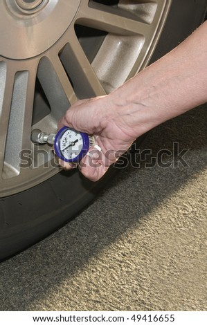Woman checking her tire pressure to help increase her  gas mileage gauge indicates low pressure - stock photo