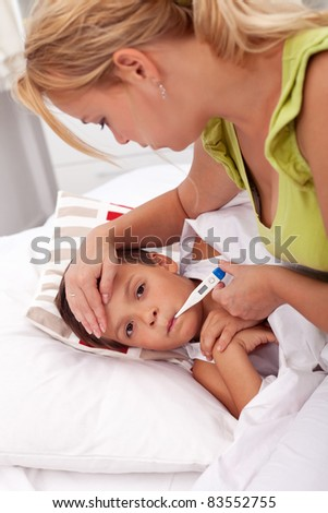 Woman checking little laying boy's temperature - stock photo