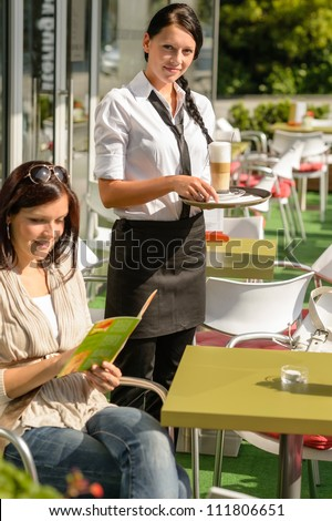 Woman checking menu waitress bringing order coffee cafe bar smiling - stock photo