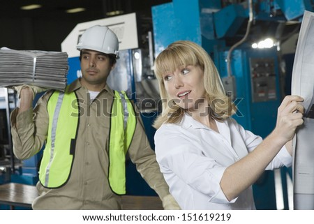 Woman checking newspaper with colleague in the background in factory