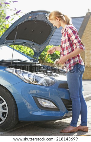 Woman Checking Oil Level In Car Engine - stock photo