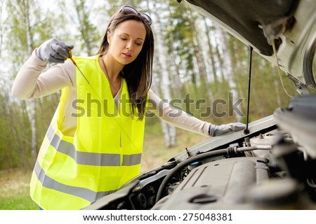 Woman checking oil level on  a roadside - stock photo