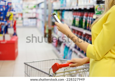 Woman checking shopping list on her smartphone at supermarket - stock photo