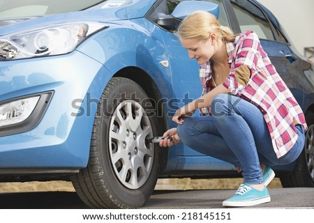 Woman Checking tire Pressure On Car - stock photo