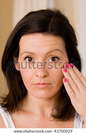Woman checks her skin in the mirror for blemishes