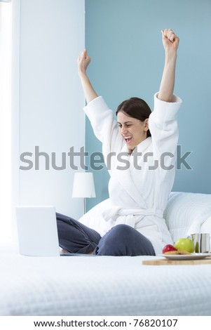 Woman cheering in bed with laptop - stock photo