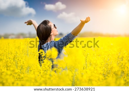 Woman cheering in the rape field  - stock photo