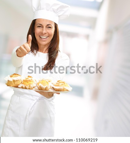 Woman chef holding baked food, outdoor - stock photo