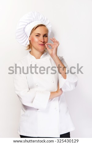 Woman chef in cook outfit showing perfect sign and smiling at camera.