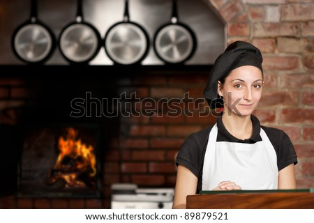 Woman Chef is standing at the kitchen entrance with the wood oven in the background in a pizza restaurant kitchen - stock photo
