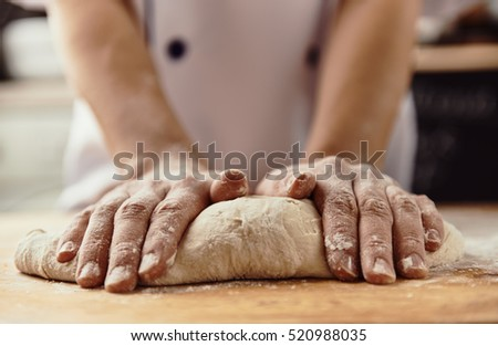 Woman chef kneading pizza dough in the kitchen.