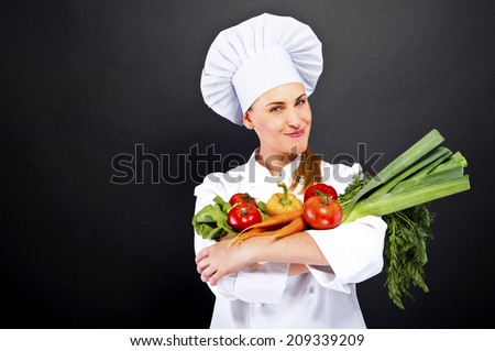 woman chef make hand heart sign with tomato over dark background - stock photo