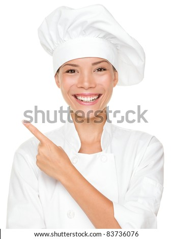Woman chef pointing / showing empty blank copy space isolated on white background. Beautiful young mixed race Asian Caucasian female model smiling happy.