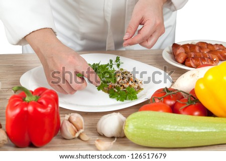 Woman chef puts vegetables on a plate
