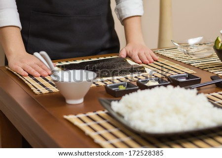 Woman chef ready to prepare japanese sushi rolls, with principal ingredients in the foreground. Selective focus in nori seaweed. - stock photo