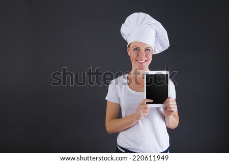 woman chef with tablet over dark background - stock photo