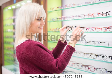 Woman choose eye glasses and trying different designs