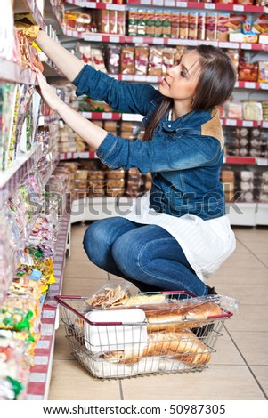 Woman choose food in grocery supermarket - stock photo