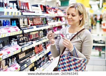 Woman chooses a pink liquid lipstick in shop - stock photo