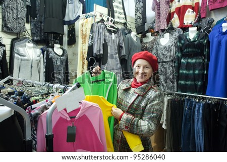 Woman  chooses clothes at fashionable shop - stock photo
