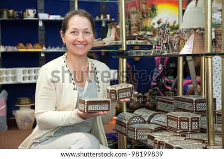Woman chooses egyptian souvenir in souvenirs shop