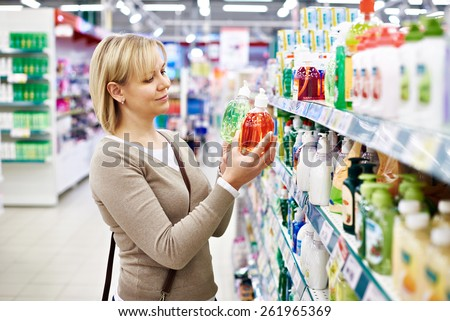 Woman chooses fragrant liquid soap in the store - stock photo