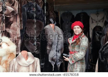 Woman  chooses fur coat at fashionable shop - stock photo