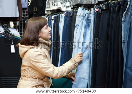 woman  chooses jeans at fashionable shop