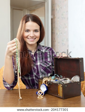 woman chooses jewelry in treasure chest at home - stock photo