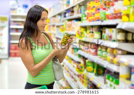woman chooses olives - stock photo