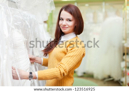 woman chooses white dress at shop of wedding fashion - stock photo
