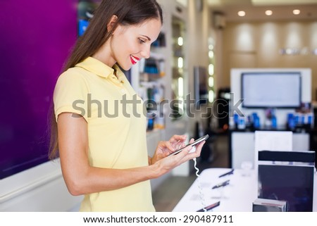 woman choosing a new mobile phone in a shop - stock photo