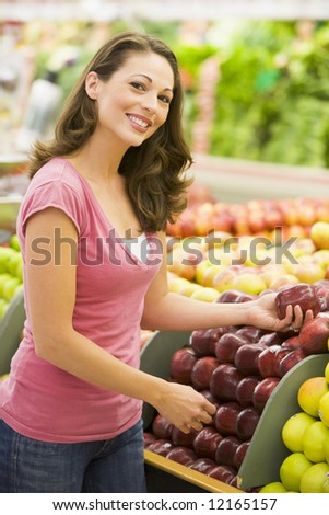 Woman choosing apples at produce counter of supermarket - stock photo