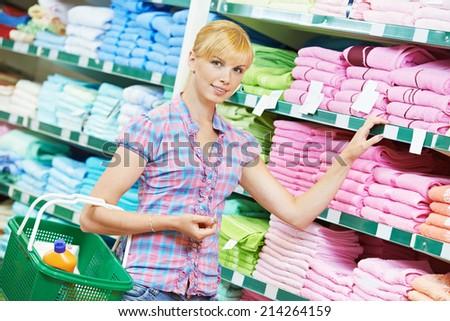 woman choosing bath towels textile in apparel clothes shop supermarket - stock photo