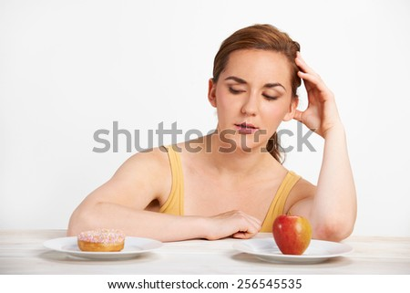 Woman Choosing Between Apple And Donut For Snack - stock photo