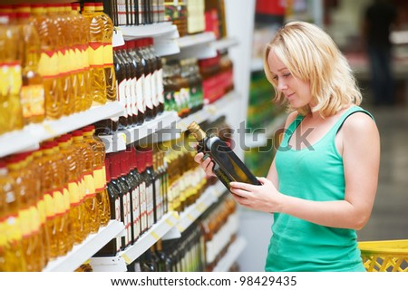 woman choosing bio food olive oil in grocery shopping store - stock photo