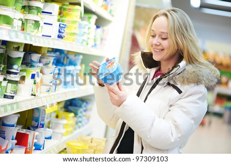 woman choosing bio food produces in dairy shopping mall - stock photo