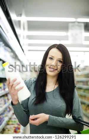 Woman choosing bottle of milk at supermarket - stock photo