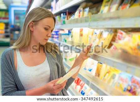 Woman choosing cheese in grocery store. - stock photo