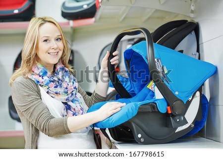 woman choosing child car seat for newborn baby in shop supermarket - stock photo