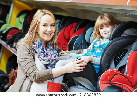 woman choosing child car seat with little girl in shop supermarket