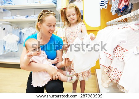 woman choosing children apparel with little baby and child girl on hands in clothing shop supermarket - stock photo