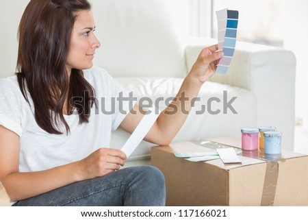 Woman choosing colour for painting the wall