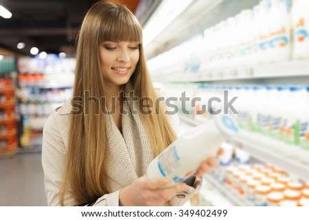 Woman choosing dairy products at supermarket - stock photo
