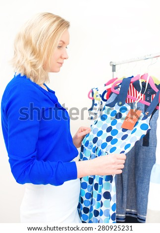 Woman choosing dress in clothing store. - stock photo
