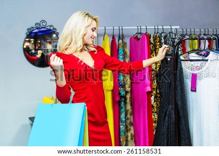 Woman choosing dress to wear in the shop. Shopping bags - stock photo