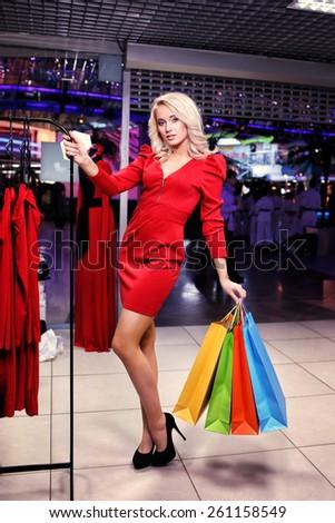 Woman choosing dress to wear in the shop. Shopping bags - stock photo
