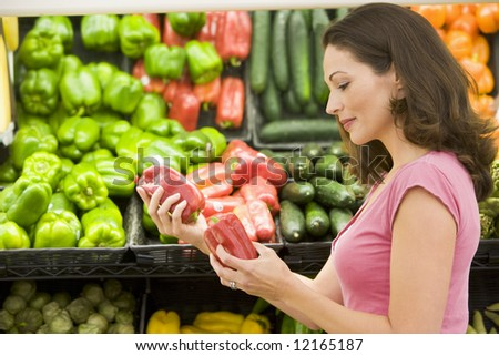 Woman choosing fresh produce in supermarket - stock photo