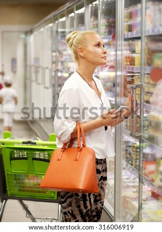 Woman choosing frozen food from a supermarket freezer. - stock photo